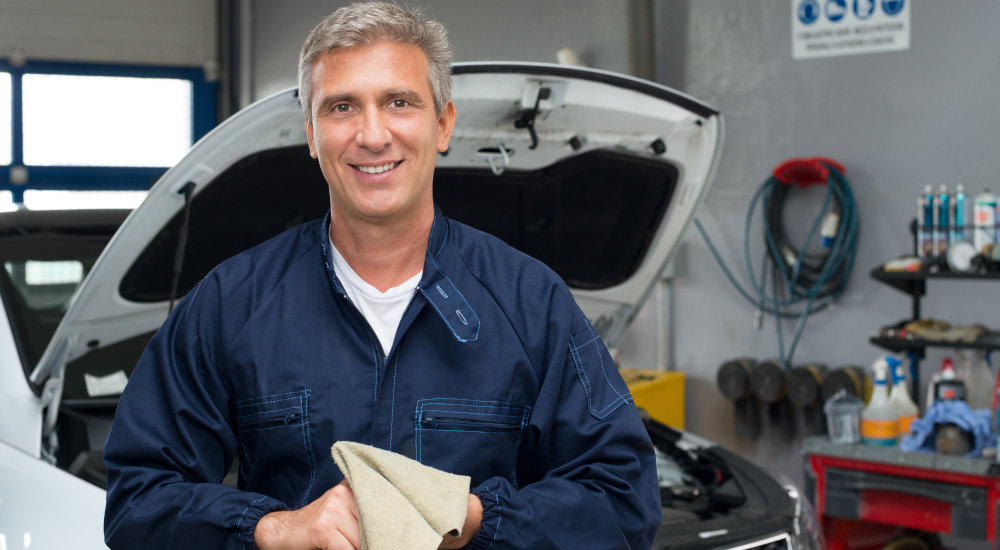 Featured image for Jobs page at Byrne Auto dotcom depicting smiling mechanic wiping hands with cloth in front of car with hood up.
