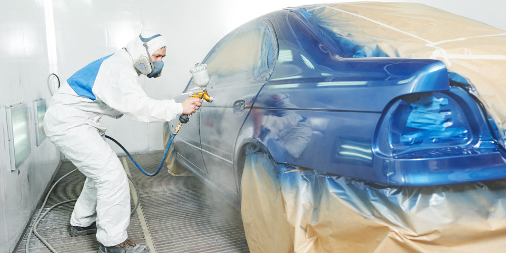 Featured image for Auto Body Technician Jobs at Byrne Auto depicting man in work suit painting a car.