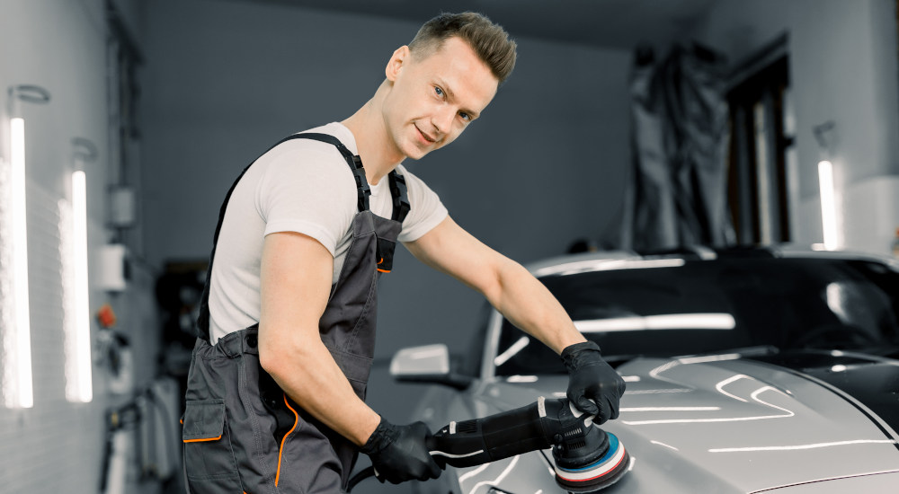 Featured image for Auto Detailer Jobs at Byrne Auto depicting man smiling at camera while buffing a car.